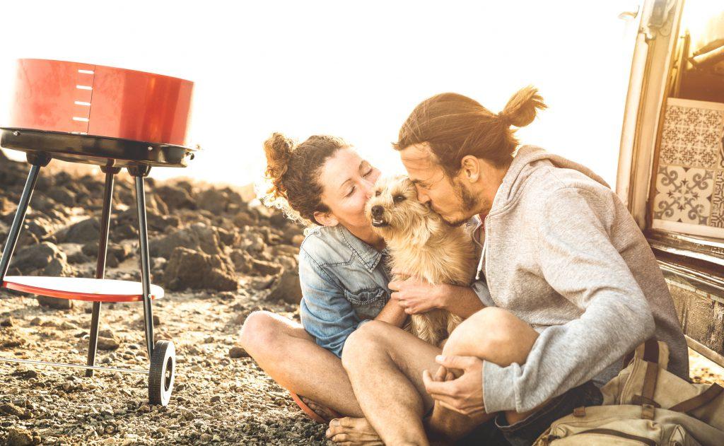couple-kissing-dog-on-beach